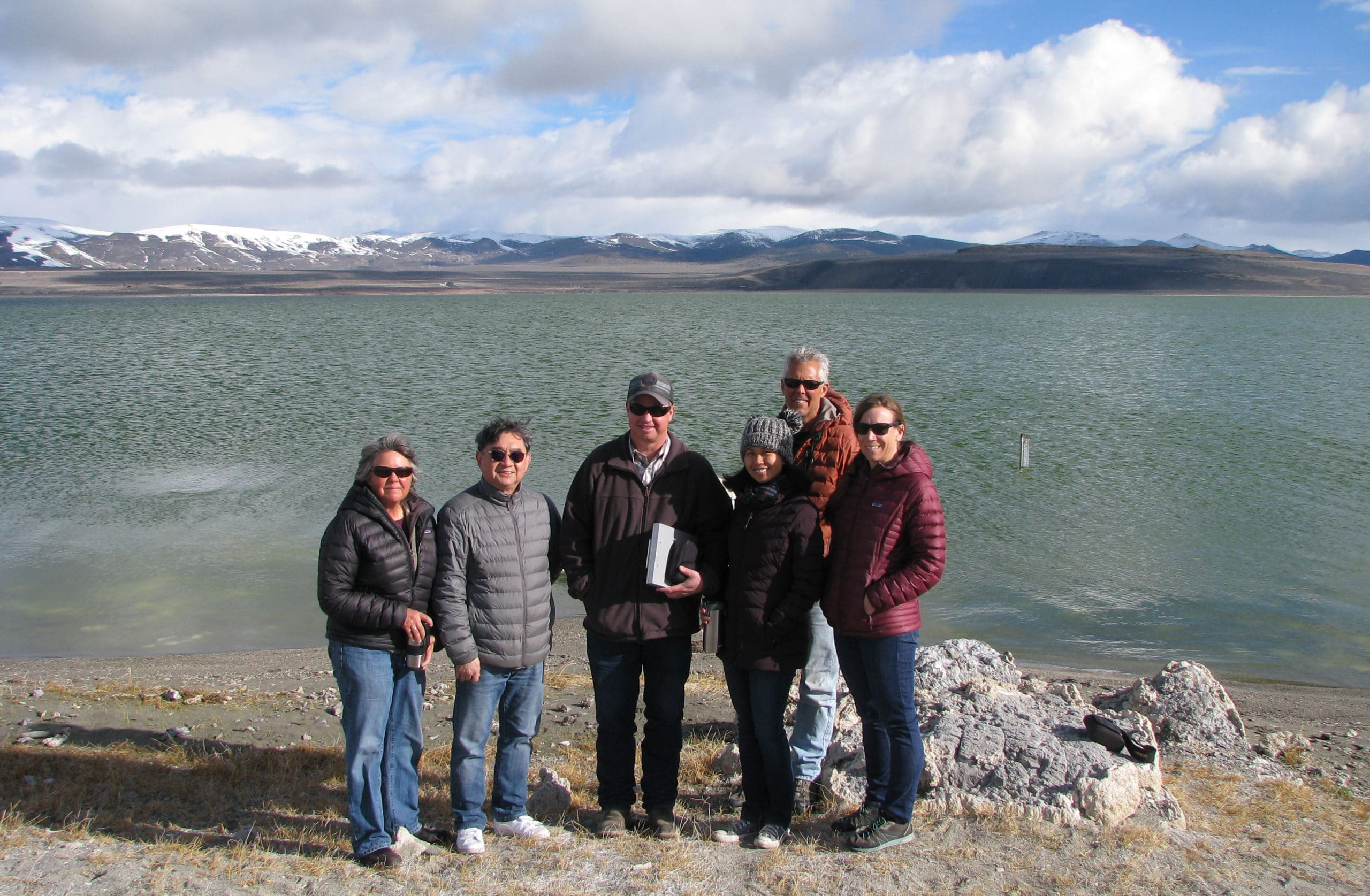 Six people standing together smiling for the camera at the shore of Mono Lake with the lake level gauge in the lake in the background and snowy hills and puffy clouds in the sky.