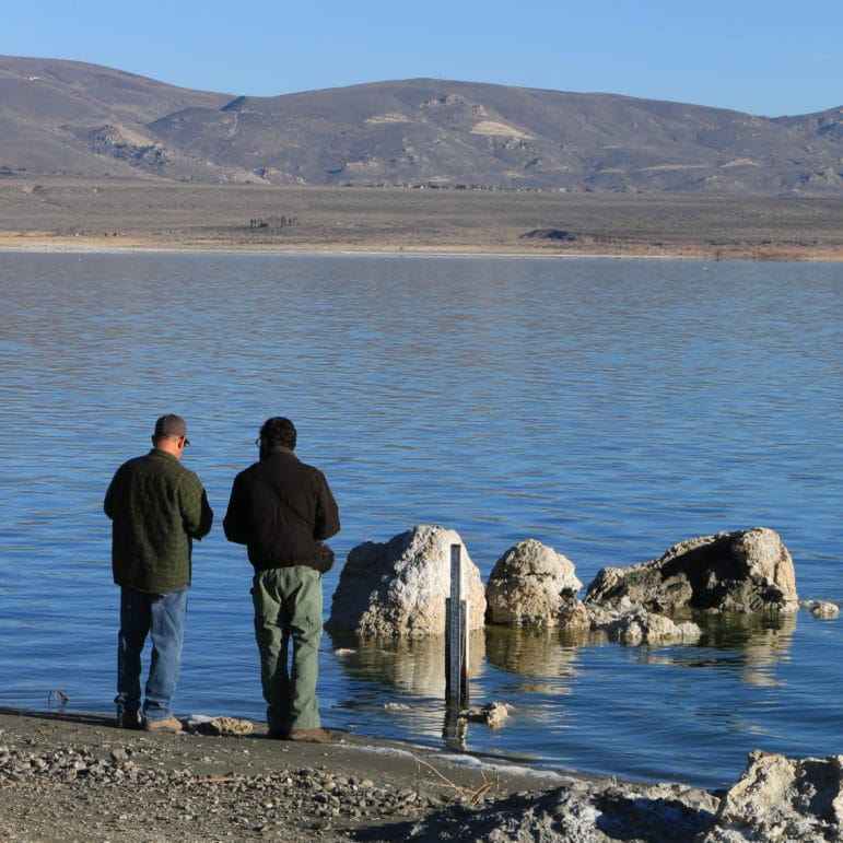 Two people stand next to each other on the shore of Mono Lake and seem to be conferring as they stand in front of a lake level gauge.