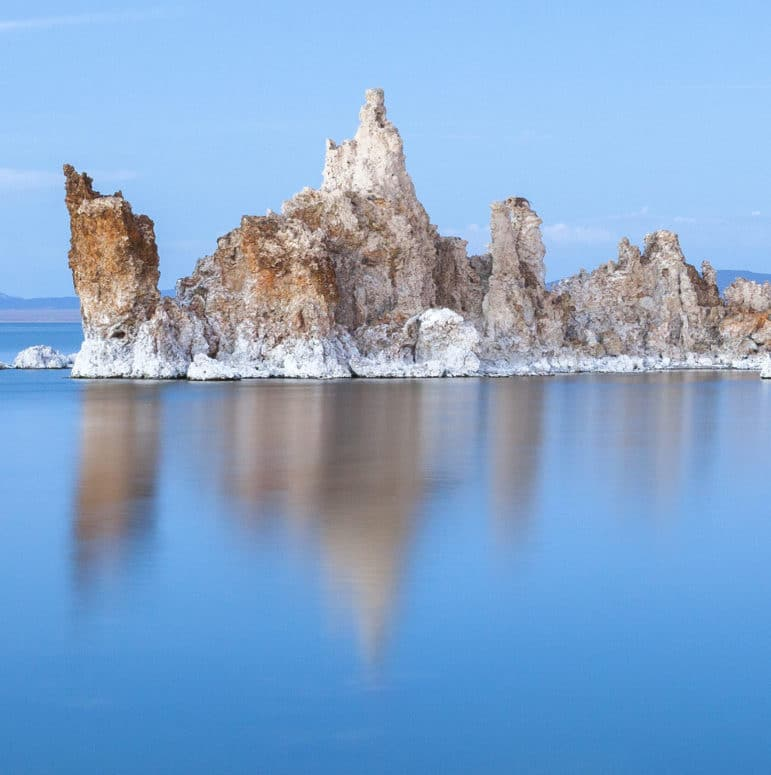 An island of white and rusty-brown tufa stands above the brilliant blue silky water of Mono Lake with a subtle blue sky.