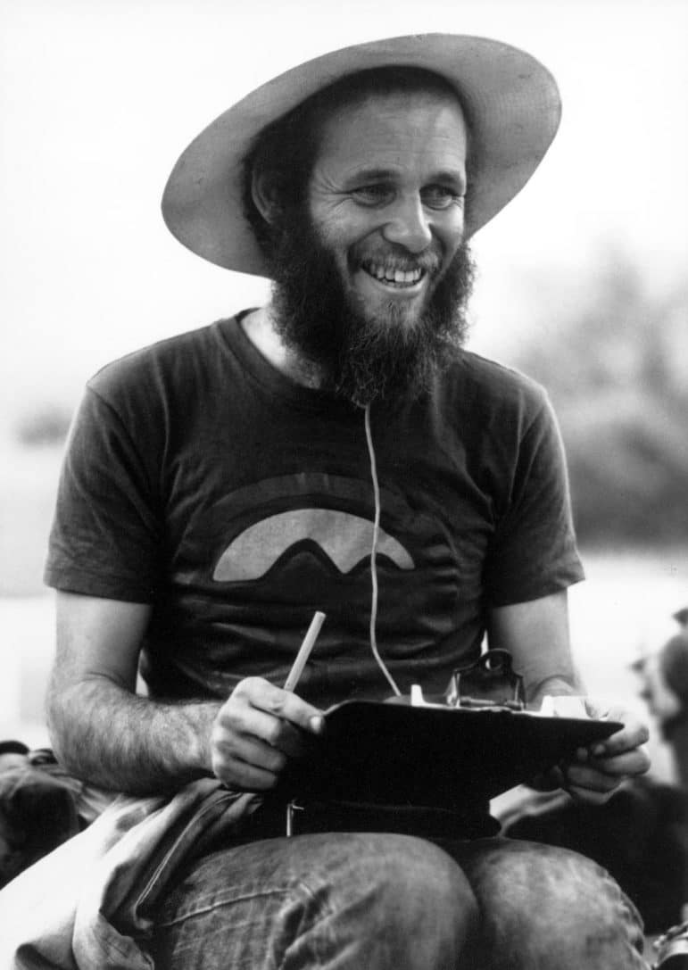 Black and white image of David Gaines with a beard, a hat, and a clipboard, with a big smile on his face.