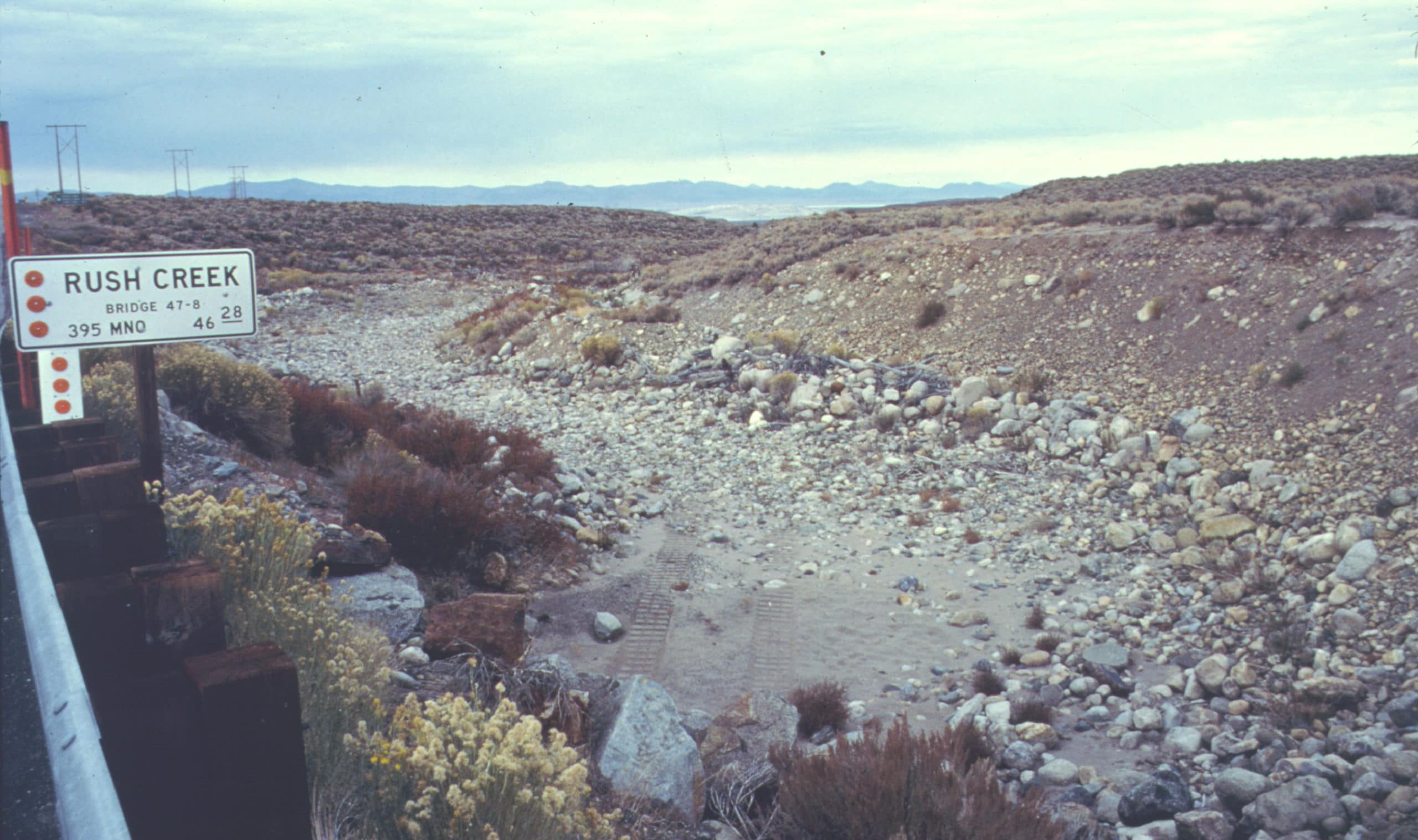 """A dry creek bed with a highway sign that reads """"Rush Creek"""" and motorized vehicle tracks in the sand of the creek below."""