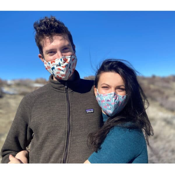 Two people with their arms around each other wearing masks and looking at the camera.