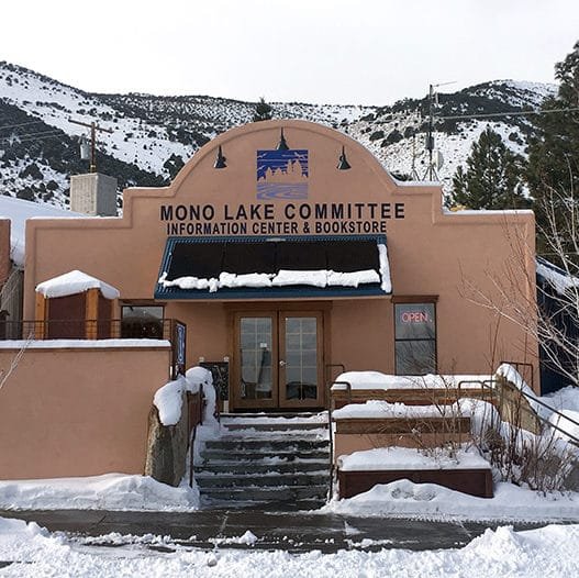 The storefront facade of the Mono Lake Committee Information Center & Bookstore after a recent snow, with snow piled on benches and solar panels but shoveled from the sidewalk and steps up the the building with an open sign in the window.