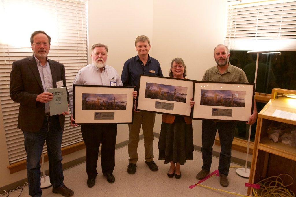 Four men and one woman stand smiling in a room, each holding framed pictures of the tufa at Mono Lake. The man to the left is holding a smaller book.