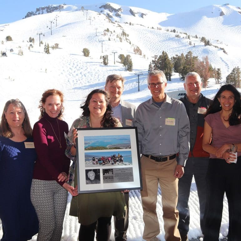 Eight people stand together for a group photograph with one person, Elsa Lopez, holding a framed award, and everyone is smiling with a large snow-covered ski mountain behind them.