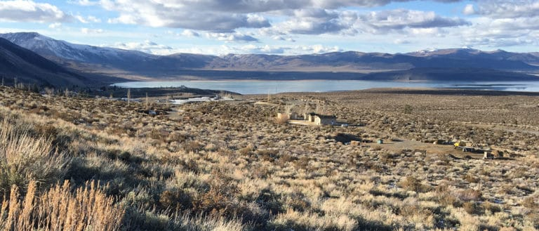 A few small houses sit in a dry green and yellow sagebrush field with a blue lake, dark mountains and a cloudy sky in the background.
