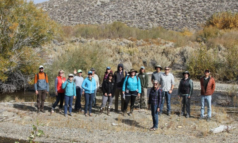 Sixteen people stand on a sand bar in a creek while wearing outdoor gear and waving on a bright sunny day in a wild riparian area of the Mono Basin.