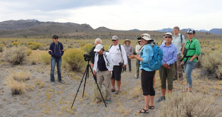 Twelve people gathered around a spotting scope and looking off into the distance on a sandy path in front of geologic craters in the background.