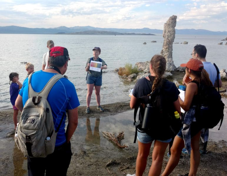 Eight people, including kids, gather around a tour guide holding a color chart while standing on a sandy strip of Mono Lake shoreline with a tall tufa tower and Mono Lake behind her as the group looks on.