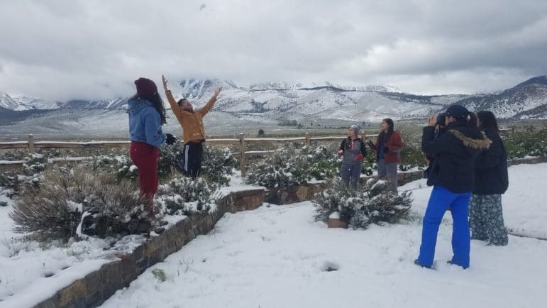 Six students stand in a circle outside in the snow with one jumping up and throwing a snowball in the air while the others laugh and take photos, with beautiful snowy mountains shrouded in clouds in the background.