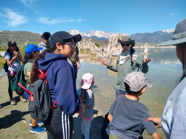 A tour guide gives a tour at the shore of Mono Lake with eight people, including kids, listening to her talk as she stands with tufa towers nearby and snowy mountains in the distance on a clear sunny day.
