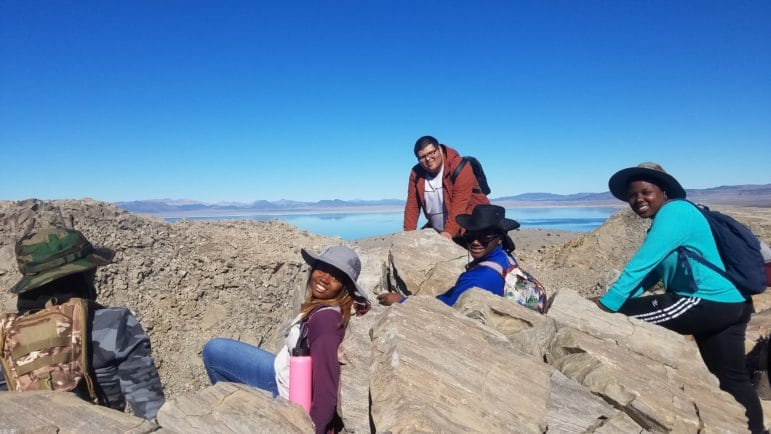 Five students on top of a rocky mountain in hiking gear looking out over Mono Lake under a clear blue sky, and they are looking happy and proud and relaxed.