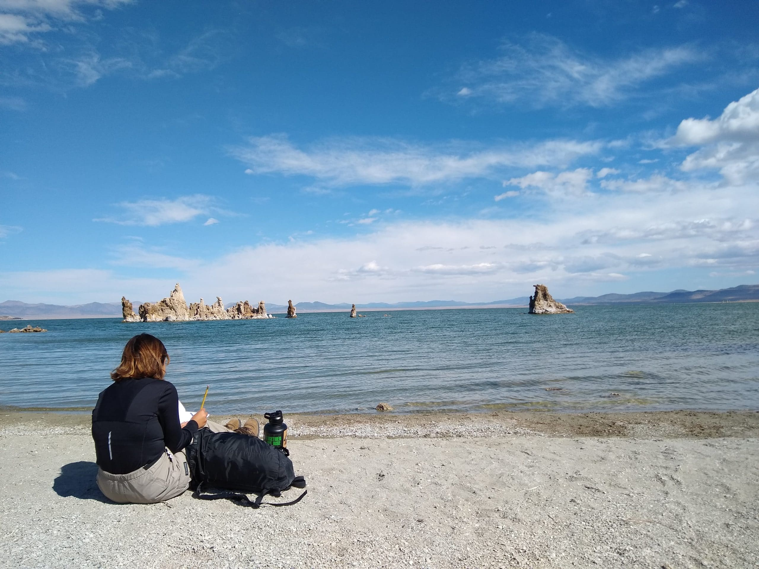 A student sits facing Mono Lake with her backpack as she writes in a journal with blue Mono Lake and an island of tufa towers and a blue sky with white clouds above.