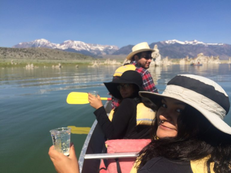 Three students sitting in a canoe on Mono Lake looking at the camera with clear plastic cups filled with Mono Lake water in their hands, smiling on a beautiful day with glassy green and blue water around them and tufa towers and mountains in the distance.