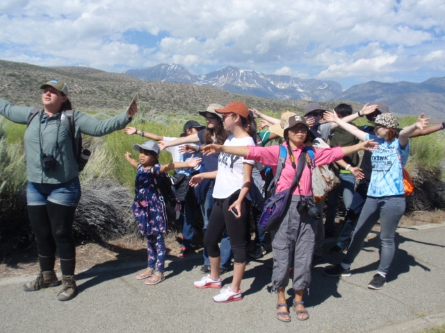 A tour guide stands in front of a group of students on a trail outside on a beautiful sunny day and they are all facing the same direction with their arms outstretched as if hugging the world.