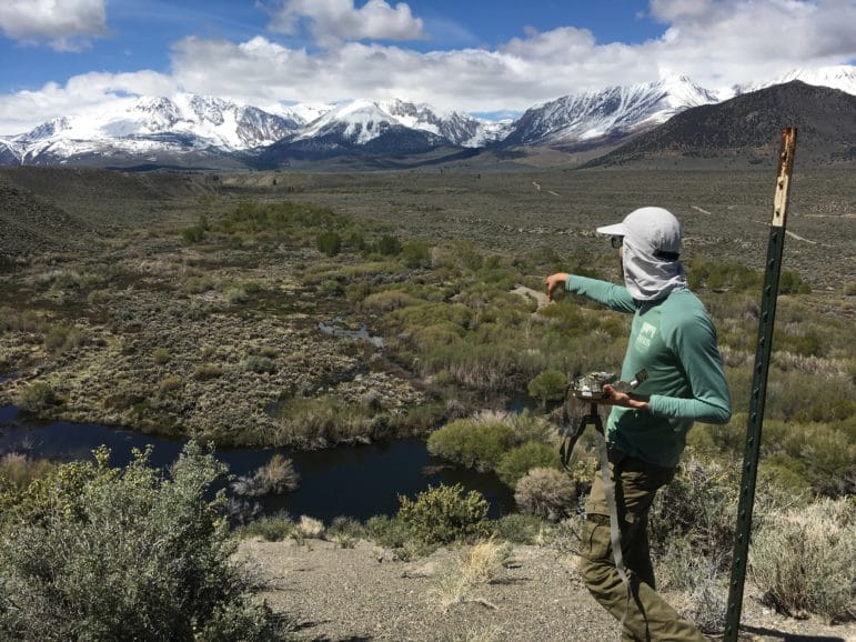 A person stands on a bluff overlooking a wide stream system with water flowing and green vegetation below and snow-capped mountains in the distance and he has a wildlife camera in his hand and is pointing to a place off in the distance.