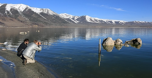 Two people kneel at the shore of Mono Lake and look out, one with binoculars, at a lake level gauge just off shore, with a glassy blue lake and snow-capped mountains in the background.