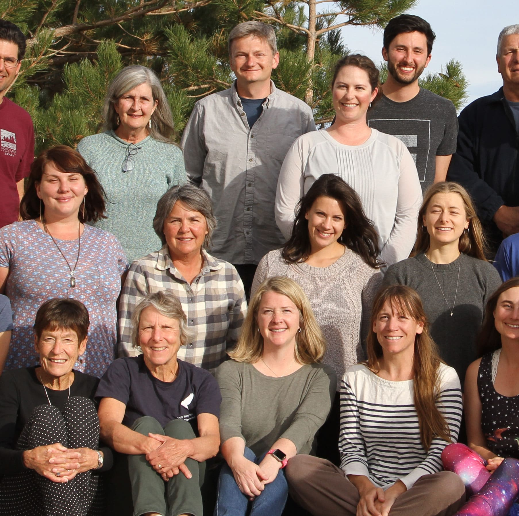 The Mono Lake Committee staff poses for a group photo ouside and are smiling and looking happy and proud.