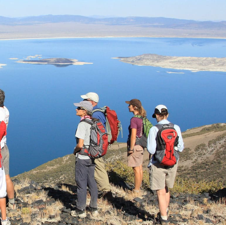 Nine people wearing backpacks and carrying binoculars on a promontory looking out over a dramatic overview of Mono Lake.