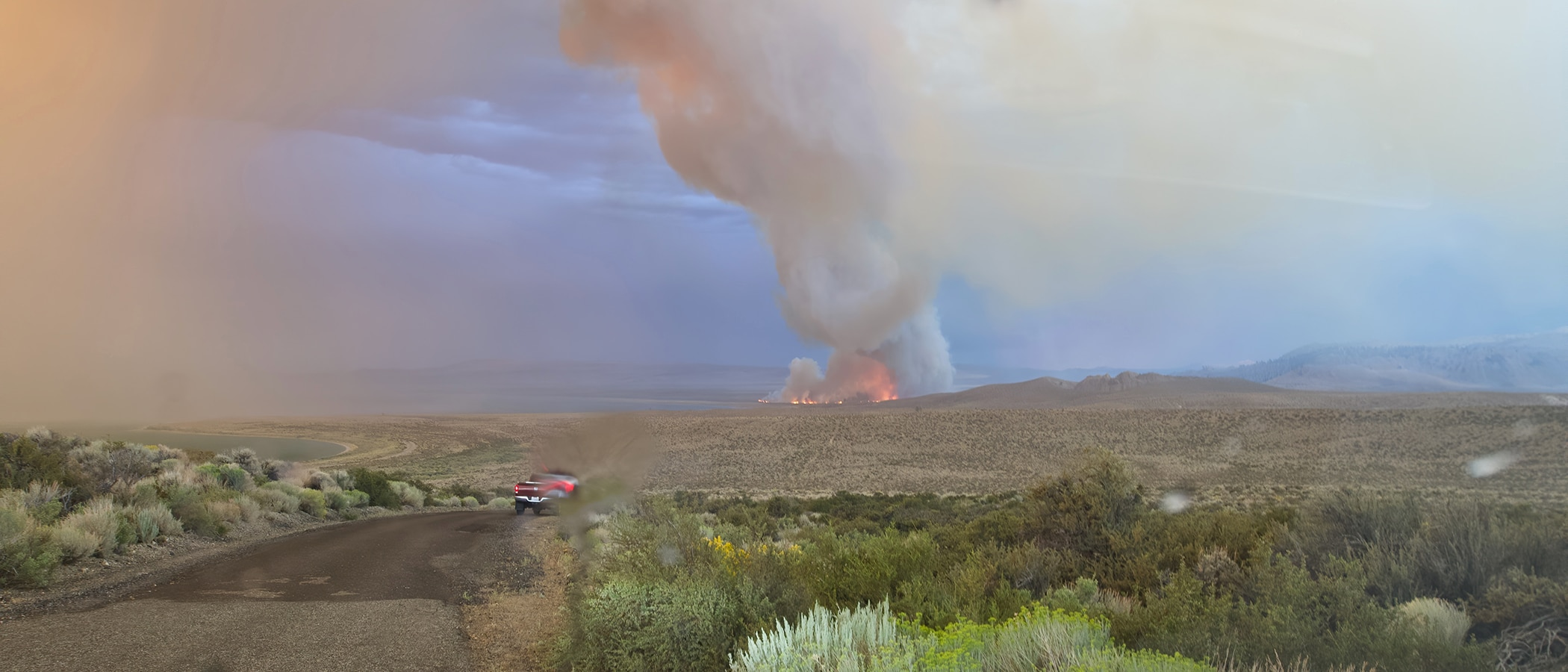 Wildfire flames and plume of smoke along the shore of Mono Lake in the distance with a truck driving down a contry road towards the fire.