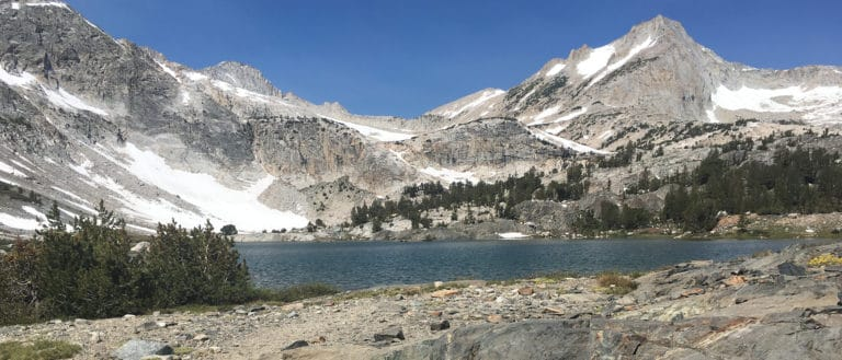 Blue Saddlebag Lake in the foreground with high alpine granite mountains with patches of snow in the background.