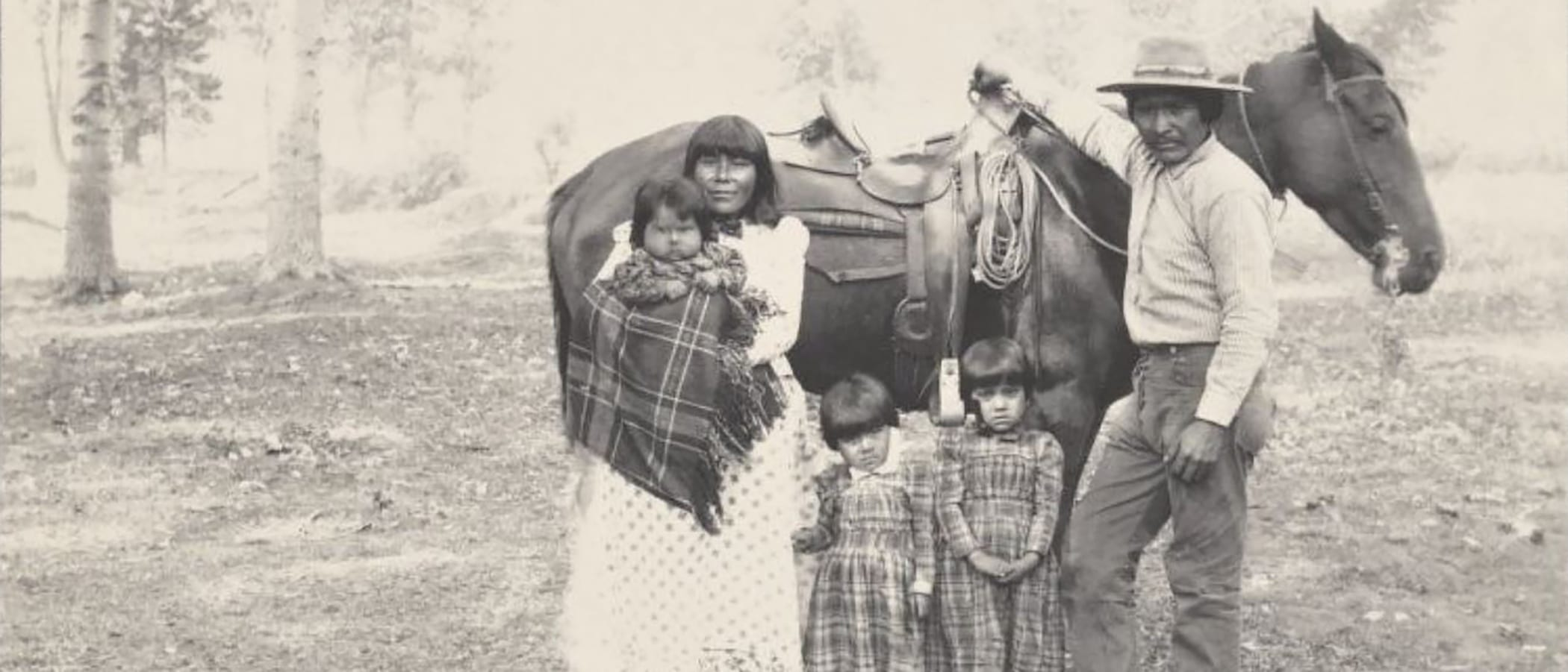 A Kutzadika'a family with a Mother, baby in arms, two young firls, and a Father stand in front of a saddled horse.
