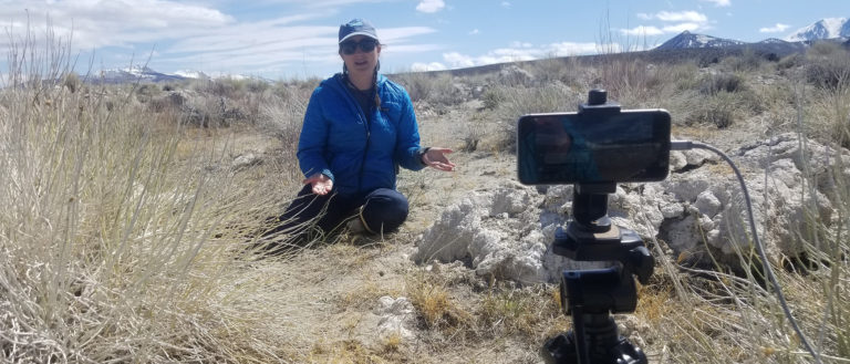 A person in a blue jacket sits in the dry grass and talks to an Iphone which is propped up on a tripod.