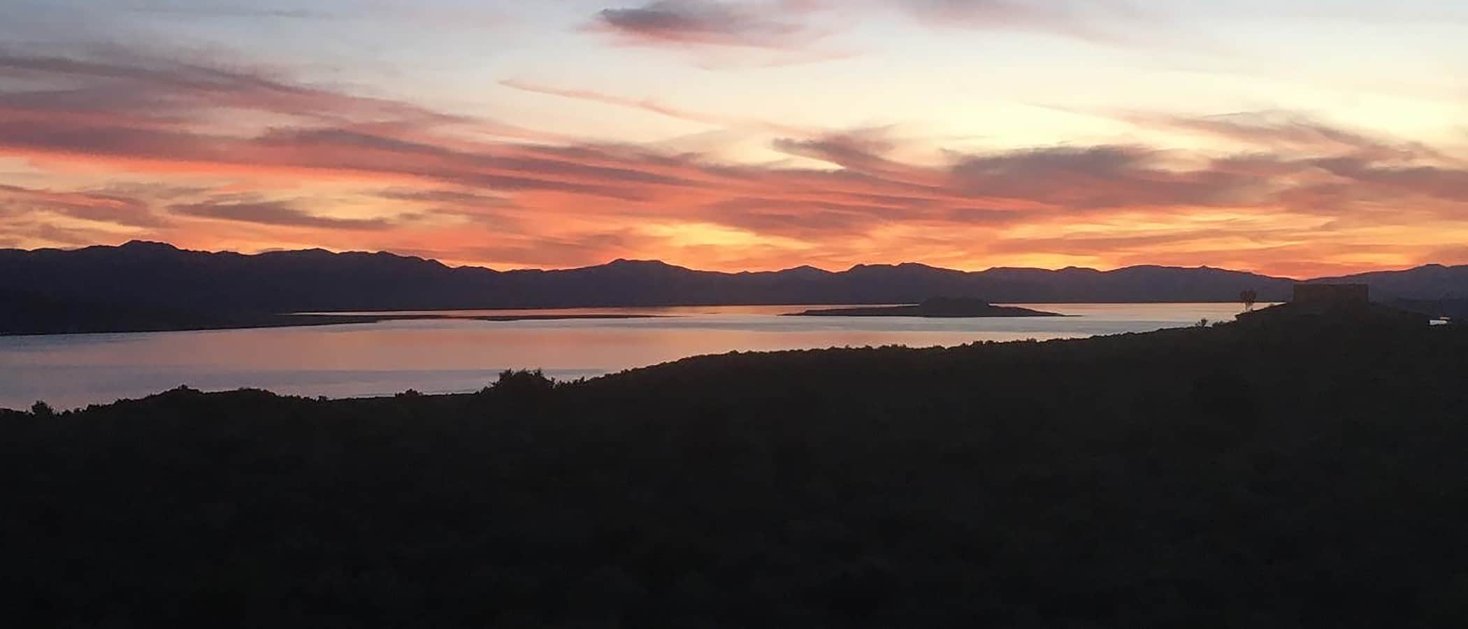 Coral pink and orange sunset stretches across the sky above silhouetted mountains and Mono Lake.