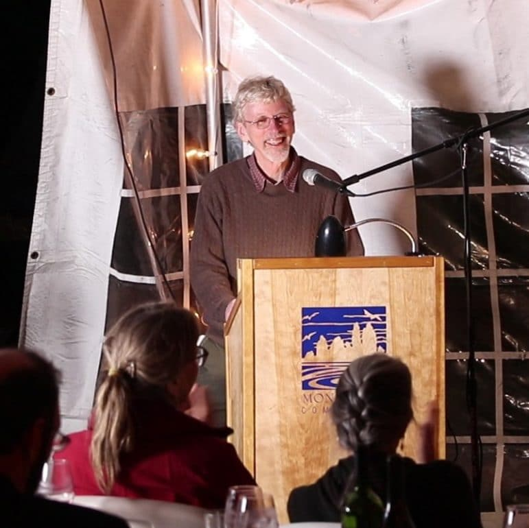 A man, Peter Vorster, stands at a lecturn, smiling, inside of an event tent with people looking on.