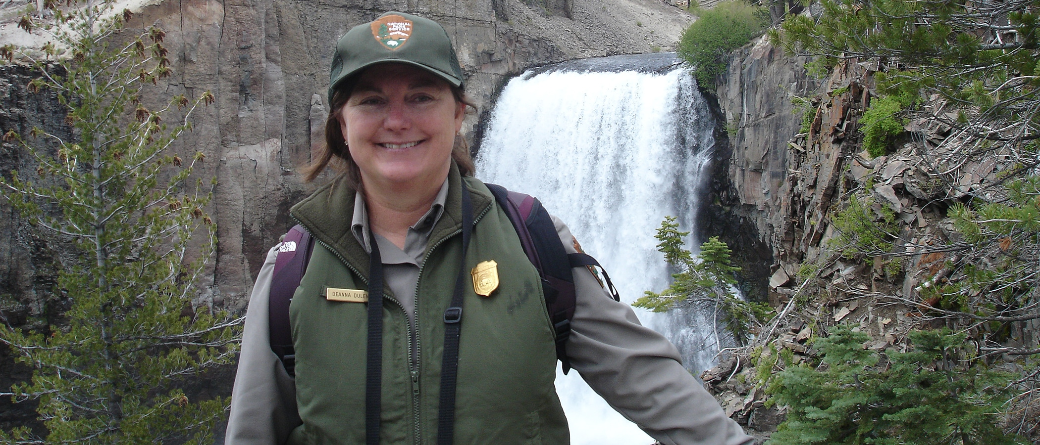 Woman in a National Park Service vest and ball cap standing in front of a large waterfall.