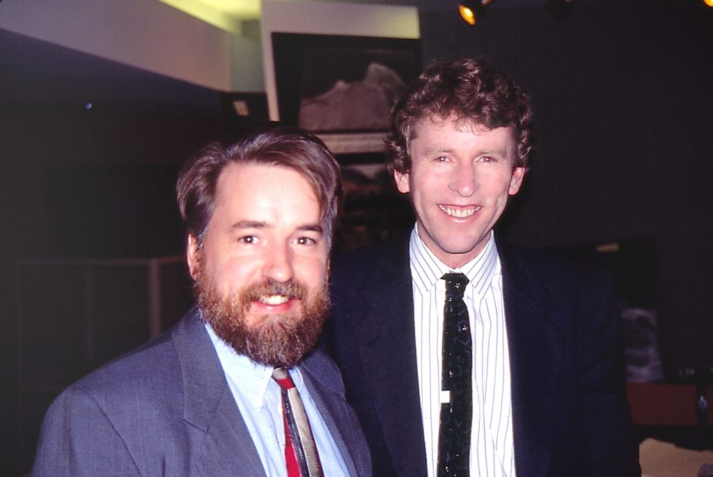 Two smiling people standing next to each other wearing suits and ties.