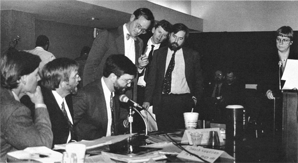 Black and white, a group of men in suits, three sitting and three standing, deliberate at a table strewn with papers. A woman standing at a podium to the right looks at them.