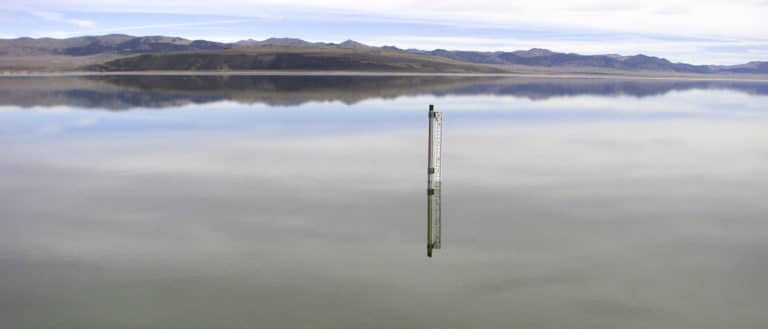 A lake level gauge, made of a metal pipe with a ruler-like measuring stick attached, pokes up from the surface of a very glassy and highly reflective lake with the lenticular-shaped Black Point and desert mountains in the background.