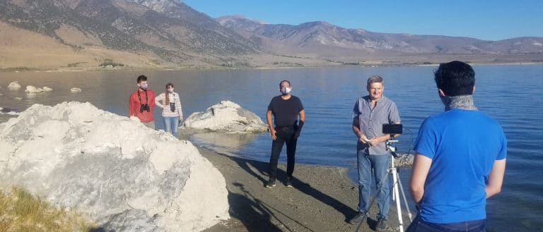 Five people standing at the shoreline of Mono Lake, socially distanced and masked, shooting a video from a cell phone on a tripod with a glassy Mono Lake and the Sierra Nevada behind them.