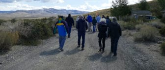 A group of about 12 people wearing cool-weather jackets walking on a dirt road near the site of the Tioga Inn development project.