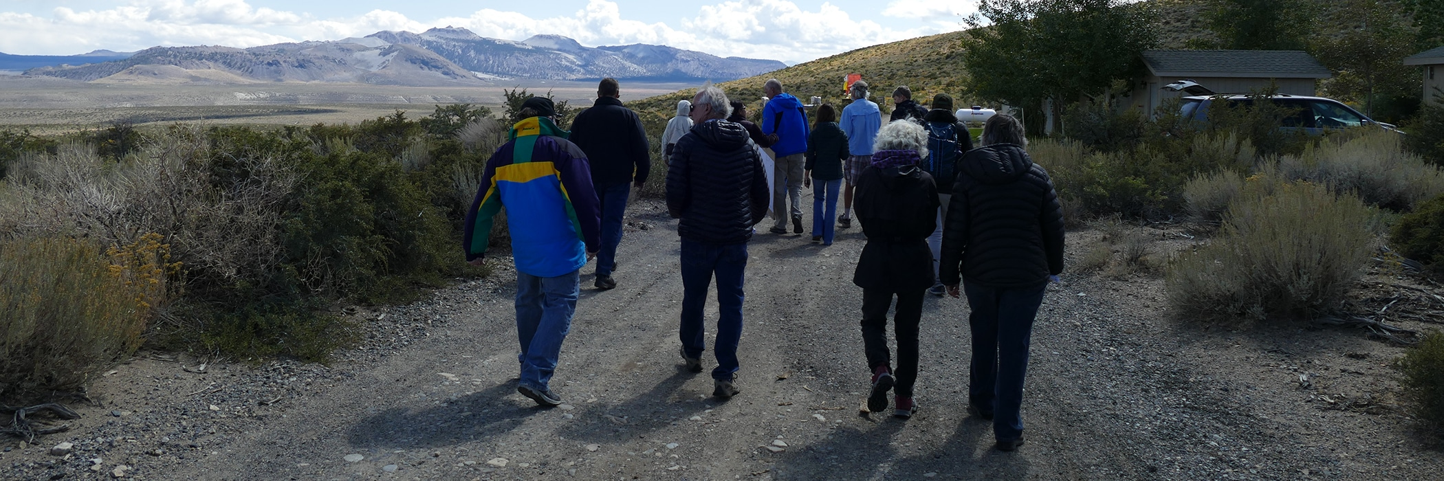 A group of people walk away from the camera down a gravel road through light green and darker green sagebrush. The Sierra Nevadas sit in a cloudy sky.