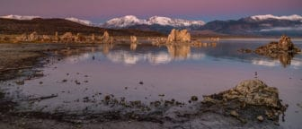 Shoreline of Mono Lake looking west towards the Sierra Nevada with tufa towers reflecting on the glassy lake and the sky is pink, purple, and blue.