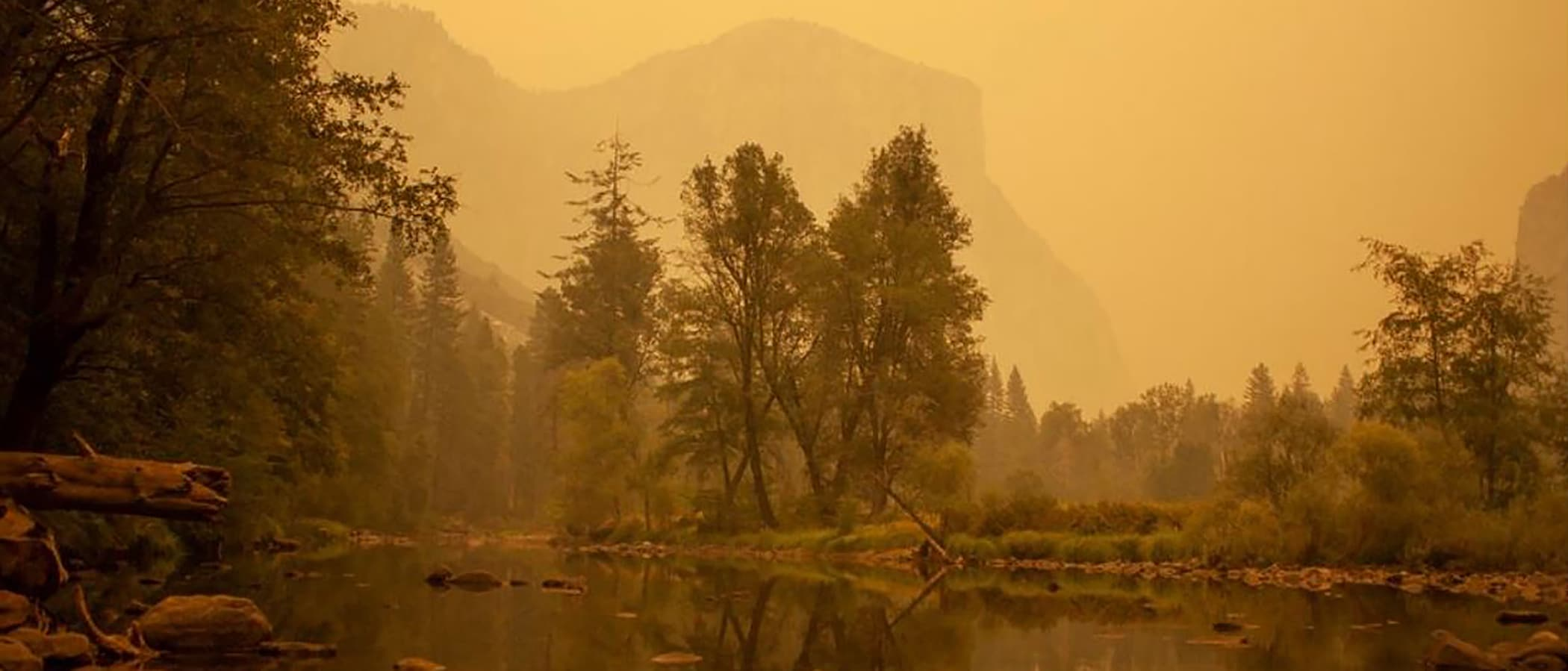 View of the Merced River flowing through a very smokey Yosemite Valley with orange smoke hanging in the air and coloring everything in muted hues.