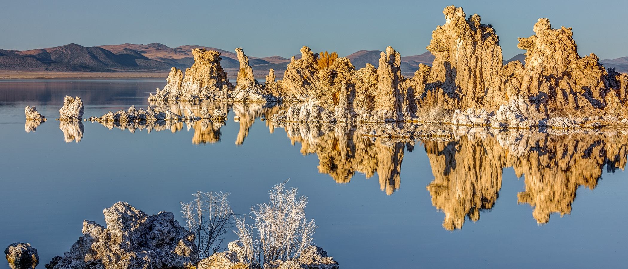 Brightly lit tufa towers reflecting in a perfectly glassy Mono Lake.