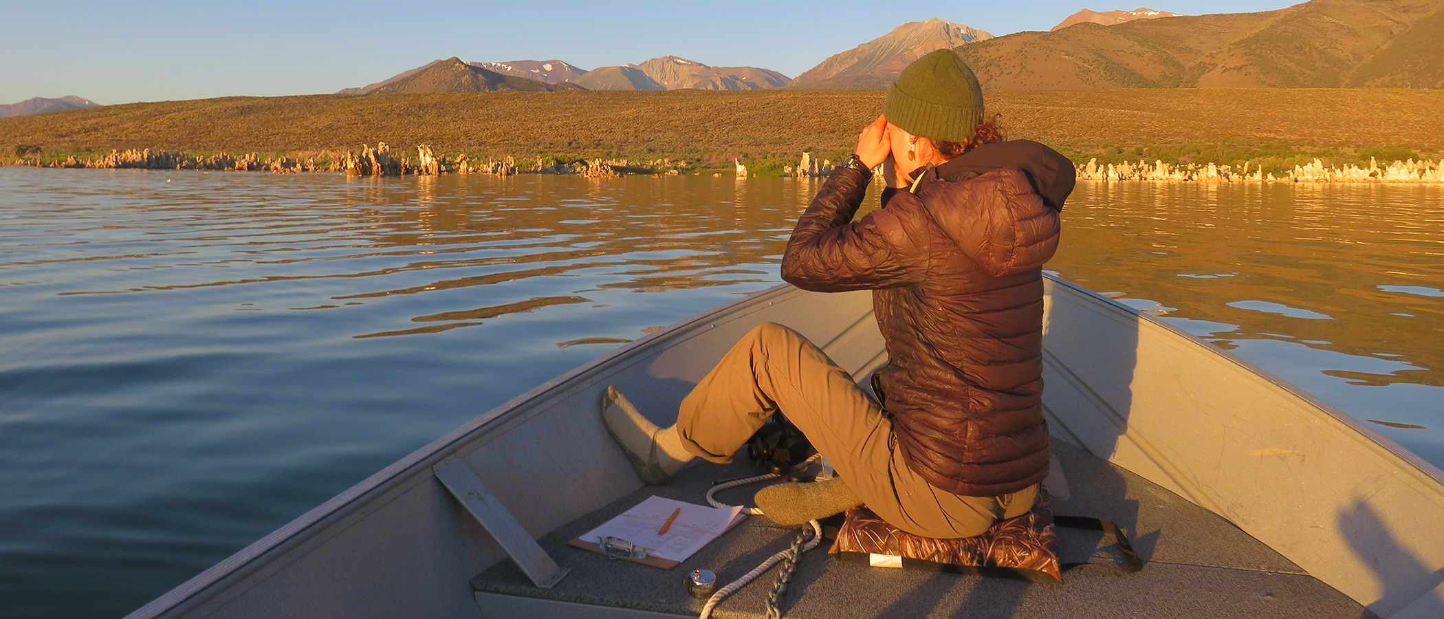 Person sitting on a boat looking out at Mono Lake in the early morning sun with the mountains in the background.
