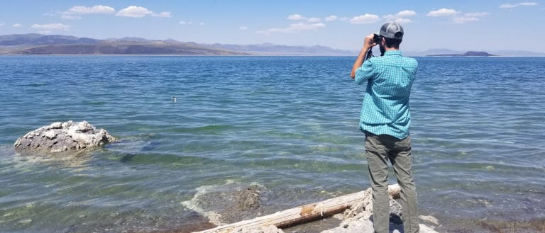 A man in a blue shirt faces away from the camera on the edge of clear and wavy turquoise water, and looks through binoculars.