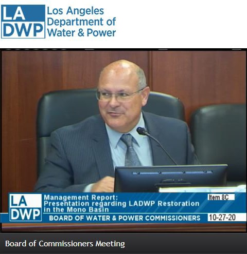 A screenshot from the Board of Commissioners Meeting shows a bald man in a suit speaking.
