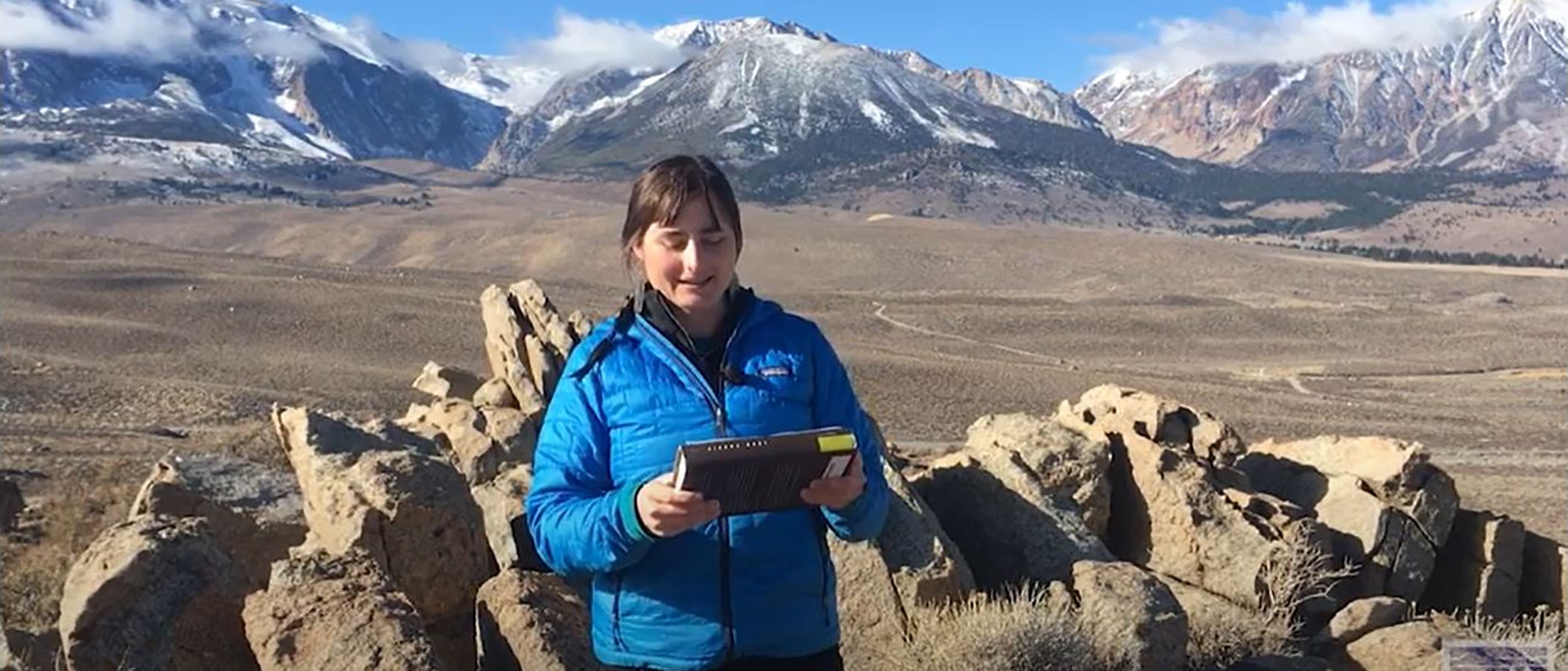 A woman with brown hair and a blue coat stands in front of a rocky vista looking out on brown fields and mountains. She is holding a book.