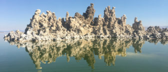 A large group of tall, light brown tufa towers juts our of the dark green water into a cloudless blue sky. The towers' reflection ripples below.