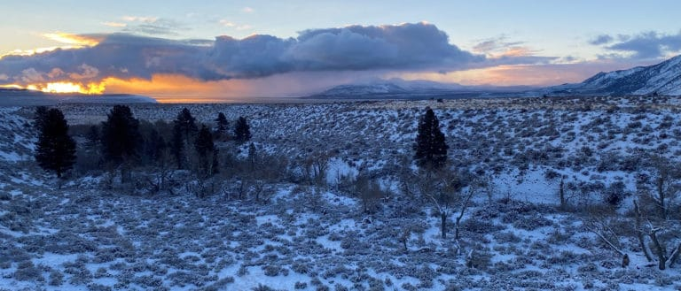 a snow speckled valley stretches ahead, bordered by mountain's edges, and the glowing orange and pink sunset peeks out behind long fluffy clouds.
