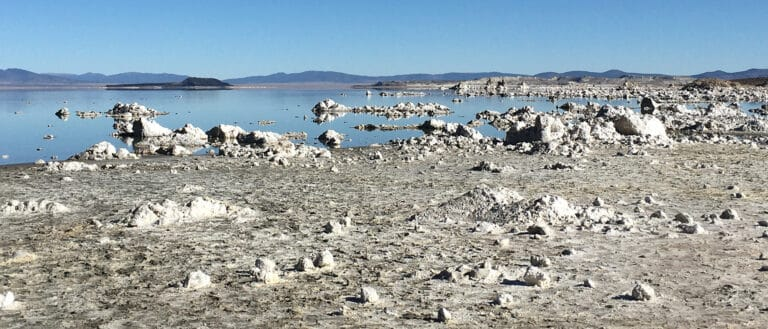 Small rocky tufa pieces are scattered across a beach and in the blue water, which reflects a clear sky.