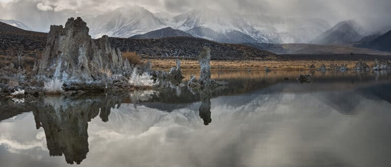 Gray clouds hang over the snowy mountains behind still, dark, tufa filled lake water.