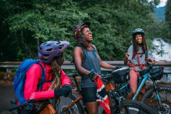 Three women on bikes and wearing backpacks and helmets laugh and smile.