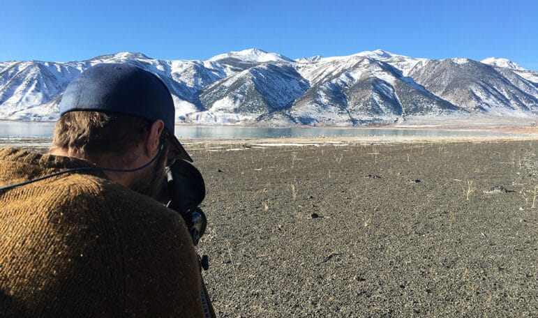 The back of a man's head as he looks at the black rock shore of Mono Lake through binoculars. Snow covered mountains are in the background.