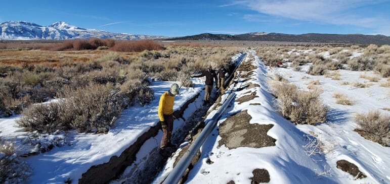 Three men are standing and walking in a long trench which stretched behind them through a snowy field of sage brush. A gray pipe sits nearby.